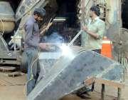 لاہور: فرروز پور روڈ پر کاریگر تعمیراتی کام میں استعمال ہونے والی مشینری ..