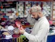 لاہور: مسجد شہداء کے باہر ایک شہری نماز کی ادائیگی کے لیے ٹوھی خرید ..