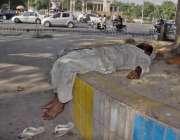 لاہور: ایک بھکاری دوپہر کے وقت چیئرنگ کراس چوک میں درخت کے سائے کے نیچے ..