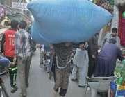 لاہور: ایک محنت کش خاتون گنبد روڈ پر بھاری سجاوٹی سامان سر پر اٹھائے ..