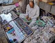راولپنڈی: ایک محنت کش روڈ کنارے انگوٹھیوں کا سٹال سجا رہا ہے۔