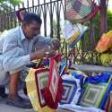 ملتان: ایک محنت کش سڑک کنارے ہاتھ ہاتھ سے بنے پنکھے فروخت کے لیے سجائے بیٹھا ہے۔