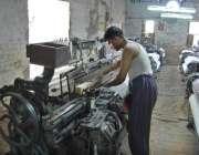 فیصل آباد: مزدور پاور لوم پر کام میں مصروف ہے۔