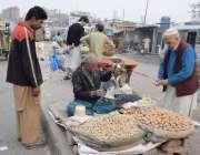 لاہور: ایک شہری فٹ پاتھ پر سجی دکان سے اخروٹ خرید رہا ہے۔