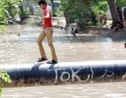 لاہور: ایک بچہ نہر کے اوپر لگے پائپ سے گزر رہا ہے۔