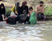 لاہور: ایک فیملی گرمی کی شدت سے بچنے کے لیے نہر میں نہا رہی ہے۔