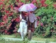 راولپنڈی: خواتین گرمی اور دھوپ کی شدت سے بچنے کے لیے چھتری تانے جا رہی ..