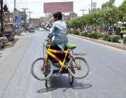 ملتان: ایک بچہ وہیل چیئر پر سائیکل رکھے لیجا رہا ہے۔