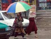 پشاور: بچیاں گرمی کی شدت سے بچنے کے لیے چھتری تانے جا رہی ہیں۔