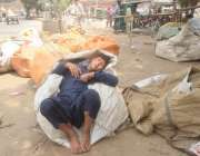 لاہور: ایک محنت کش بچہ نیند پوری کر رہا ہے۔