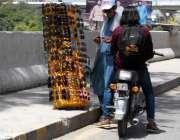 راولپنڈی: شہری روڈ کنارے لگے سٹال سے دھوپ سے بچاؤ کے چشمے خرید رہاہے۔