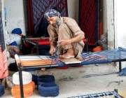 فیصل آباد: ایک معمر محنت کش چارپائی بنا رہا ہے۔