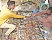 لاہور: بھاٹی چوک میں سڑک کنارے لگی دکان سے ایک نوجوان انگوٹھیاں پسند ..