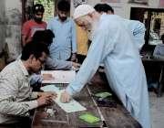 حیدر آباد: عام انتخابات 2018  ایک بزرگ شخص بیلٹ پیپر حاصل کرنے کے لیے بیلٹ ..