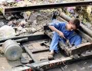 لاہور: ایک خانہ بدوش بچہ اپنے ریڑھے کی مرمت میں مصروف ہے۔