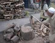 لاہور: ایک بزرگ لکڑیاں کاٹ رہا ہے، سوئی گیس پریشر میں کمی کے باعث لکڑیوں ..
