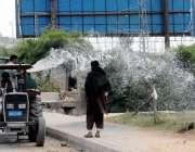 راولپنڈی: پی ایچ اے اہلکار روڈ کنارے سبزہ زار کو پانی دے رہا ہے۔