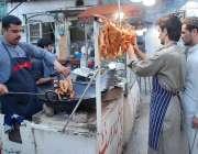 پشاور: دکاندار سڑک کنارے سٹال لگائے چکن فروخت کے لیے فرائی کر رہا ہے۔