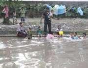 لاہور: ایک فیملی گرمی کی شدت کم کرنے کے لیے نہر میں نہا رہی ہے۔