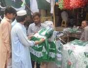 لاہور: ایک شخص اردو بازار میں یوم آزادی کی مناسبت سے بچوں کے کپڑے خرید ..