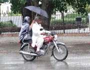 سرگودھا: موٹر سائیکل سوار فیملی بارش سے بچنے کے لیے چھتری تانے اپنی ..
