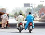 ملتان: موٹر سائیکل سوار ایک خراب موٹر سائیکل کو دھکا لگارہا ہے۔