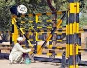 ملتان: ریلوے اہلکار پھاٹک کو رنگ کرنے میں مصروف ہے۔