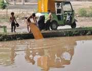 لاہور: ایک شخص نہر کنارے اپنے بچوں کے ہمراہ رکشہ دھو رہا ہے۔