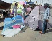 کراچی: شہری سڑک کنارے لگے سٹال سے مچھردانیاں پسند کررہا ہے۔