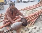لاہور: ایک محنت کش سیڑھی تیار کرنے کے لیے بانس کاٹ رہا ہے۔
