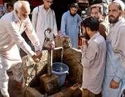 راولپنڈی: ایک معمر شہری پینے کے لیے ہینڈ پمپ سے پانی کی بالٹی بھر رہا ..
