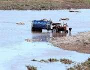 راولپنڈی: ایک شخص دریائے سواں میں ٹریکٹر ٹرالی دھو رہا ہے۔