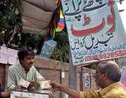 لاہور: ایک شخص سڑک کنارے نئے کرنسی چینچ کا سٹال لگائے بیٹھا ہے۔