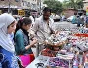 راولپنڈی: عید کی تیاریوں میں مصروف خواتین ایک سٹال سے چوڑیاں خرید رہی ..