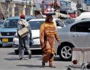 راولپنڈی: صدر بازار میں ایک محنت کش خاتون سر پر جیولری رکھے فروخت کے ..