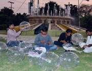 لاہور: محنت کش فروخت کے لیے غباروں میں ہوا بھر رہے ہیں۔