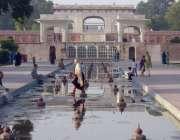 لاہور: ایک خاتون شالیمار باغ میں لگے بند فواروں کے اندر سے گزر رہی ہے۔