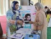 لاہور: ایک خاتون ایکسپو سنٹر میں جاری نمائش میں لگے سٹال سے معلومات ..