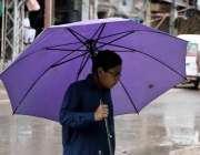 راولپنڈی: بارش سے بچنے کے لیے ایک بچہ چھتری تانے روڈ کرارس کر رہا ہے۔