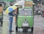 لاہور: شہر میں ہونے والی بارش کے دوران ایک ٹریفک وارڈن چھتری تانے اوور ..