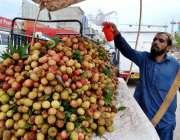 اسلام آباد: ریڑھی بان لیچی کو تازہ رکھنے کے لیے پانی کا چھڑکاؤ کر رہا ..