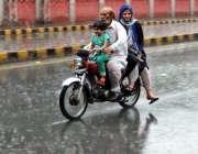 لاہور: شہر میں ہونیوالی بارش کے دوران موٹر سائیکل سوار فیملی اپنی منزل ..