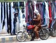 راولپنڈی: موٹر سائیکل سوار سڑک کنارے لگے سٹال سے رومال پسند کررہا ہے۔