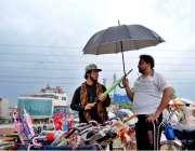 اسلام آباد: سڑک کنارے لگے سٹال سے شہری ایک سٹال سے چھتری پسند کر رہا ..