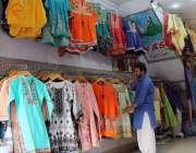 ملتان: دکاندار فروخت کے لیے نئے سلے ہوئے کپڑے سجا رہا ہے۔