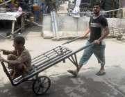 لاہور: ایک محنت کش ہتھ ریڑھی پر بچے کو بٹھا کر لیجا رہے ہیں۔