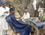 لاہور: شہری درخت کے سائے میں سجی دکان پر حجام سے بال کٹوا رہا ہے۔