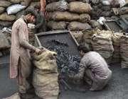 راولپنڈی: دکاندار کوئلہ فروخت کے لیے بوری میں پیک کررہے ہیں۔