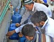 فیصل آباد: شہری واٹر فلٹریشن پلانٹ سے پینے کے لیے پانی بھر رہے ہیں۔