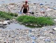 راولپنڈی: نالہ لئی سے محنت کش لڑکا کچرا چن رہا ہے۔